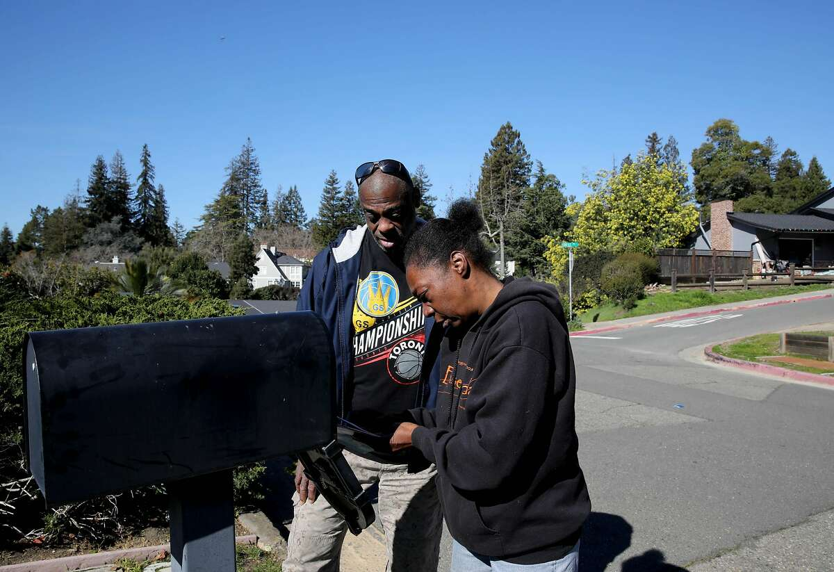 """Greg Dunston and Marie Mckinzie search for mail outside of Terry McGrath's home in Piedmont, Calif., on Wednesday, February 5, 2020. The once homeless couple lived on the streets of Oakland a year ago before McGrath invited them to live in his in-law unit. """"The only thing that's changed is our clothes and today, we're still the same,"""" Dunston said with a smile."""