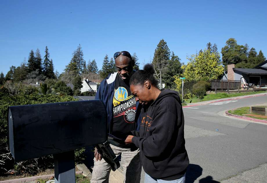 Greg Dunston and Marie Mckinzie check the mail outside Terrence McGrath's home in Piedmont. Photo: Yalonda M. James / The Chronicle