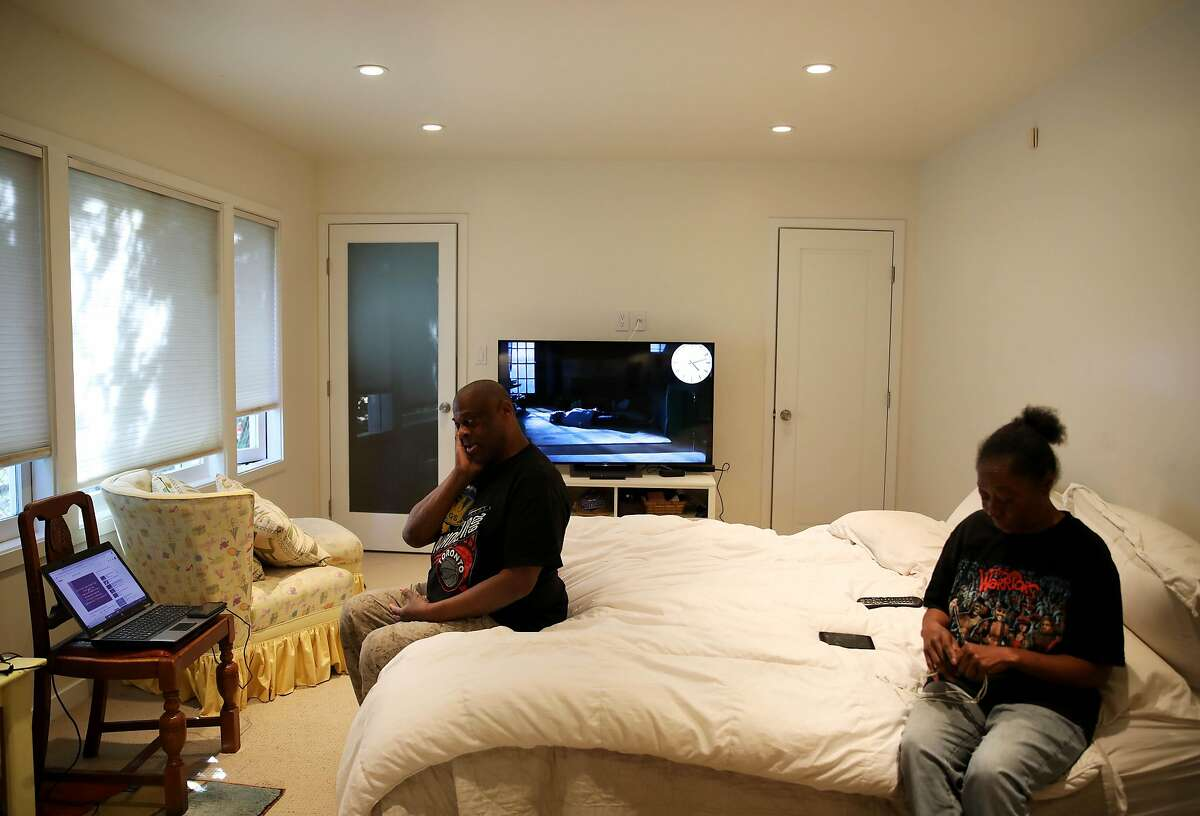 """Greg Dunston and Marie Mckinzie relax in their apartment in Piedmont, Calif., on Wednesday, February 5, 2020. The once homeless couple lived on the streets of Oakland a year ago before developer Terry McGrath invited them to live in his $4 million home. """"The only thing that's changed is our clothes and today, we're still the same,"""" Dunston said with a smile."""