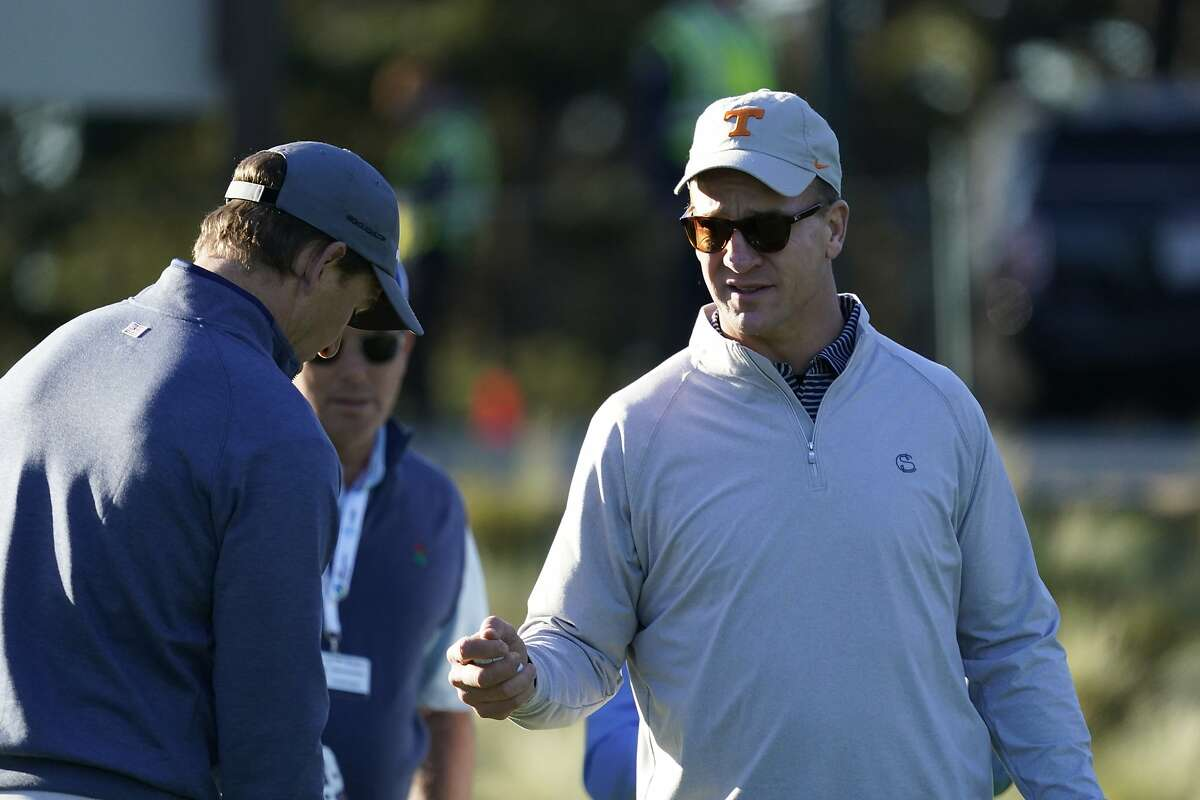 Peyton Manning, right, and Eli Manning prepare to hit from the first tee of the Spyglass Hill Golf Course during the first round of the AT&T Pebble Beach National Pro-Am golf tournament Thursday, Feb. 6, 2020, in Pebble Beach, Calif. (AP Photo/Tony Avelar)