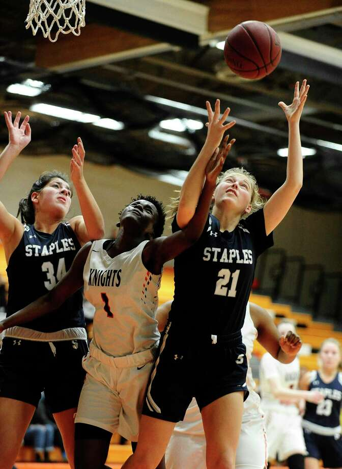 Stamford's Breanna Jacobs fights for a rebound with Staples' Ariana Gerig (34) and Marisa Shurrock (21) in the first half of Thursday's game at Kuzco Gymnasium in Stamford. Photo: Matthew Brown / Hearst Connecticut Media / Stamford Advocate
