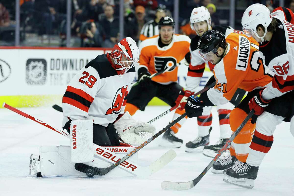 Philadelphia Flyers' Scott Laughton (21) cannot get a shot past New Jersey Devils' Mackenzie Blackwood (29) as Jack Hughes (86) defends during the second period of an NHL hockey game, Thursday, Feb. 6, 2020, in Philadelphia. (AP Photo/Matt Slocum)