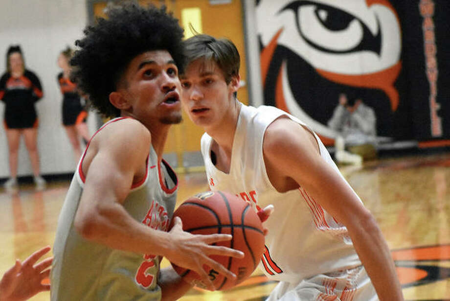 Alton's Andrew Jones drives to the basket past Edwardsville's Brennan Weller (right) in the third quarter Thursday night at Edwardsville. Photo: Matt Kamp / Hearst Midwest