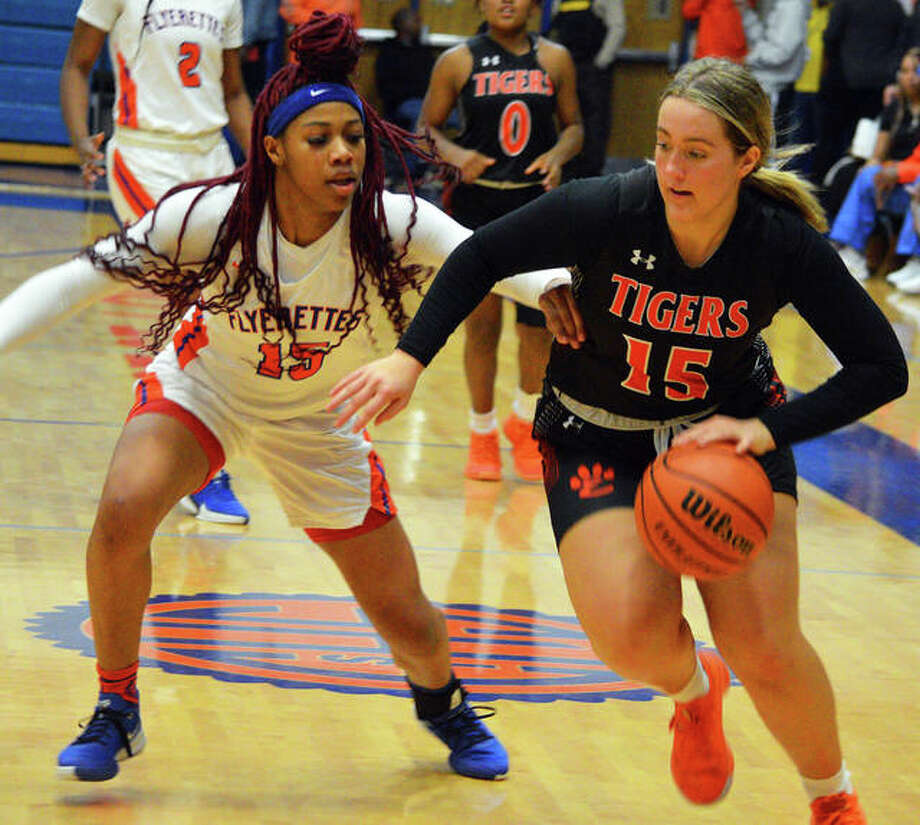 Edwardsville's Kylie Burg, right, drives to the basket during the fourth quarter of Thursday's Southwestern Conference game at East St. Louis.