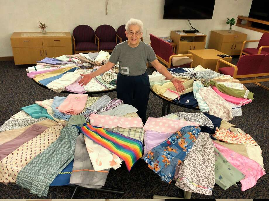 Elaine Preuss displays several of the dresses she made that have been donated to various organizations. (Provided photo)