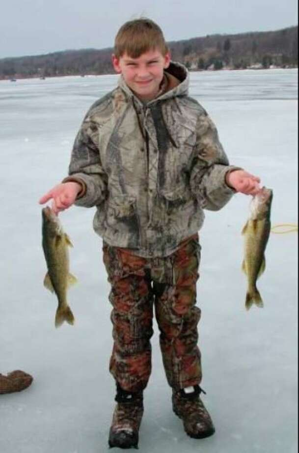 Gavin Loper of Manistee, showed off the walleye he caught on Portage Lake during the 2017 Big Ice Fishing Contest. (File photo)