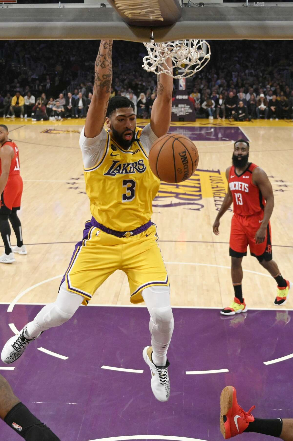 Los Angeles Lakers forward Anthony Davis dunks as Houston Rockets guard James Harden watches during the second half of an NBA basketball game Thursday, Feb. 6, 2020, in Los Angeles. The Rockets won 121-111. (AP Photo/Mark J. Terrill)