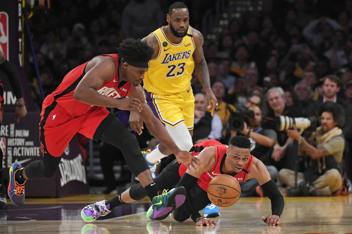 Houston Rockets guard Russell Westbrook, right, falls as forward Danuel House Jr., left, takes the ball and Los Angeles Lakers forward LeBron James watches during the second half of an NBA basketball game Thursday, Feb. 6, 2020, in Los Angeles. The Rockets won 121-111. (AP Photo/Mark J. Terrill)