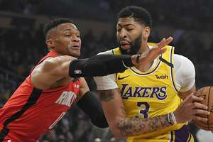Houston Rockets guard Russell Westbrook, left, reaches for the ball held by Los Angeles Lakers forward Anthony Davis during the first half of an NBA basketball game Thursday, Feb. 6, 2020, in Los Angeles. (AP Photo/Mark J. Terrill)