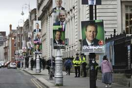 Election posters are displayed on lampposts outside the Irish Prime Minister offices in Dublin, Ireland, Friday, Feb. 7, 2020. Irish voters will choose a new parliament on Saturday, and may have bad news for the two parties that have dominated the country's politics for a century, Fianna Fail and Fine Gael. Polls show a surprise surge for Sinn Fein, the party historically linked to the Irish Republican Army and its violent struggle for a united Ireland. (AP Photo/Peter Morrison)