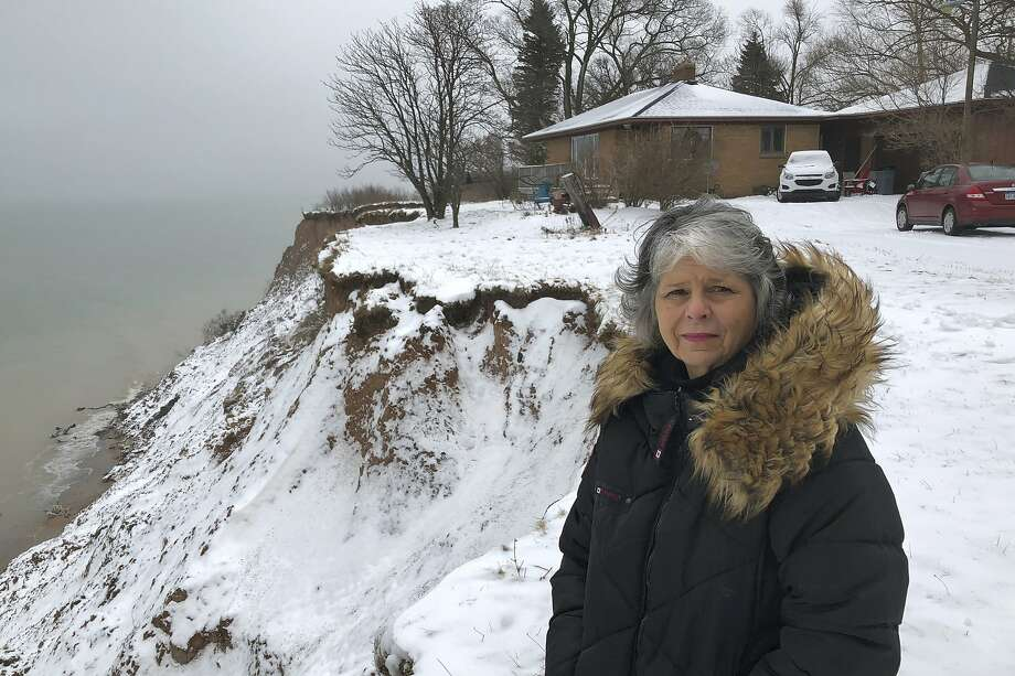 Rita Alton checks erosion of the bluff overlooking Lake Michigan next to her house Jan. 14 in the town of Manistee. More than an acre of land once separated the home from the cliff. Photo: John Flesher / Associated Press