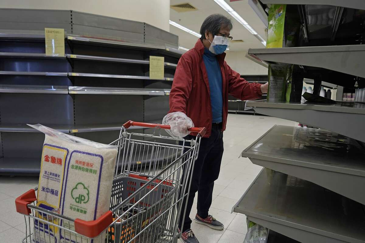 A man wearing face mask and plastic bag as a glove walks past empty shelf of tissue papers at a supermarket in Hong Kong, Friday, Feb. 7, 2020. In recent days, residents have been buying large amounts of products because they fear that border restrictions, which were enforced to control the coronavirus outbreak, may affect supply flows into Hong Kong. (AP Photo/Kin Cheung)