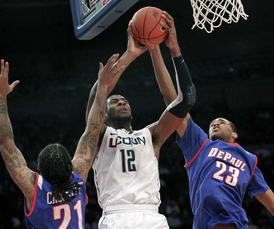 UConn's Andre Drummond, center, goes up for a shot past DePaul's Jamee Crockett, left, and Donnavan Kirk during the first round of the Big East NCAA college basketball conference tournament in New York, Tuesday, March 6, 2012. Photo: Seth Wenig / ASSOCIATED PRESS / AP2012