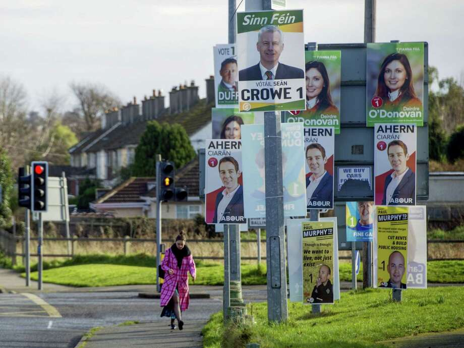 A pedestrian passes by general election posters for various political parties in Dublin on Feb. 6, 2020. Photo: Bloomberg Photo By Aidan Crawley. / © 2020 Bloomberg Finance LP