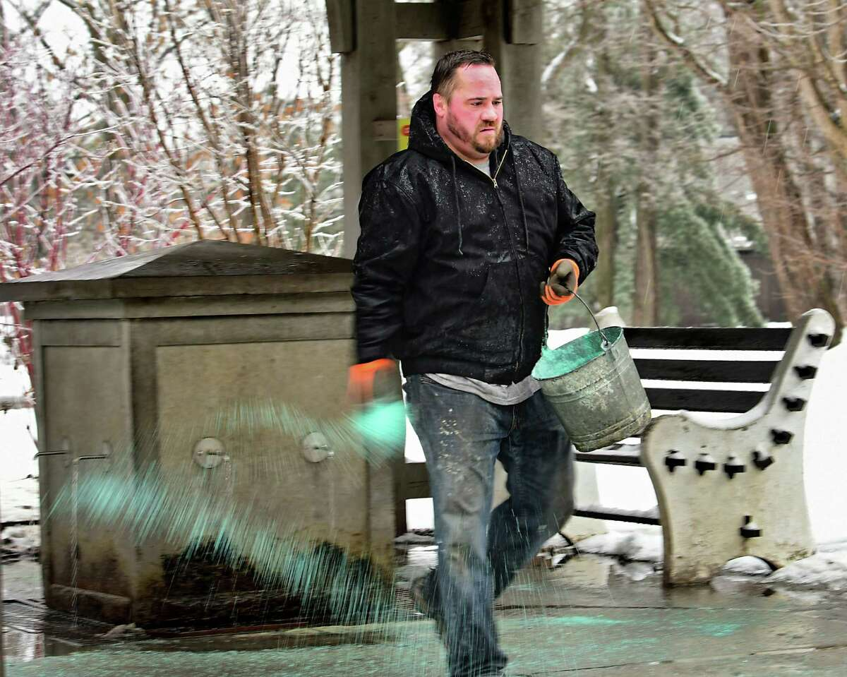 Park maintenance worker Connor Berry of Ballston Spa spreads ice melt around a popular water spring in Saratoga Spa State Park on Friday, Feb. 7, 2020 in Saratoga Springs, N.Y. Freezing temperatures caused cold rain to freeze on trees. (Lori Van Buren/Times Union)