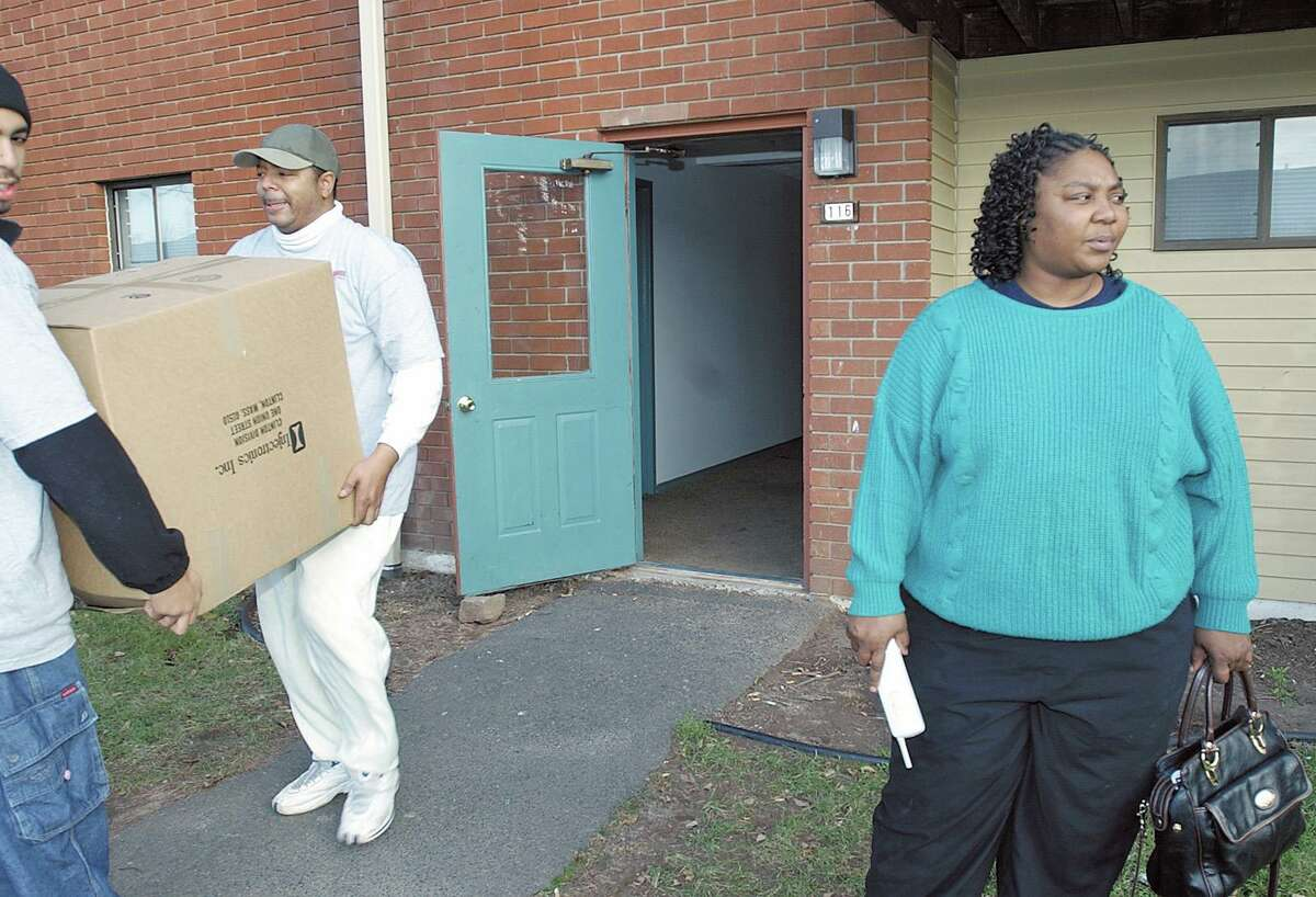 A woman stands outside her Thomas Street apartment in Middletown as movers bring her belongings out.