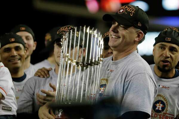 FILE - In this Nov. 1, 2017, file photo, Houston Astros manager A.J. Hinch holds the championship trophy after Game 7 of baseball's World Series against the Los Angeles Dodgers, in Los Angeles. Houston manager AJ Hinch and general manager Jeff Luhnow were suspended for the entire season Monday, Jan. 13, 2020, and the team was fined $5 million for sign-stealing by the team in 2017 and 2018 season. Commissioner Rob Manfred announced the discipline and strongly hinted that current Boston manager Alex Cora - the Astros bench coach in 2017 - will face punishment later. Manfred said Cora developed the sign-stealing system used by the Astros. (AP Photo/Matt Slocum, File)