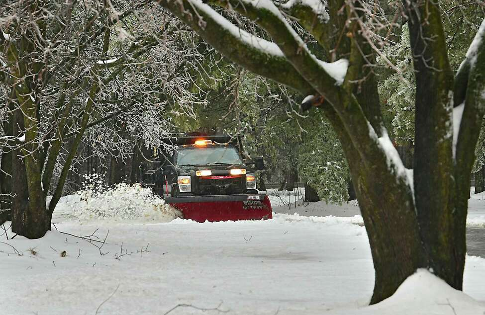 A park maintenance truck is seen through ice covered trees plowing snow off the walkway along the Avenue of Pines in Saratoga Spa State Park on Friday, Feb. 7, 2020 in Saratoga Springs, N.Y. Freezing temperatures caused cold rain to freeze on trees. (Lori Van Buren/Times Union)