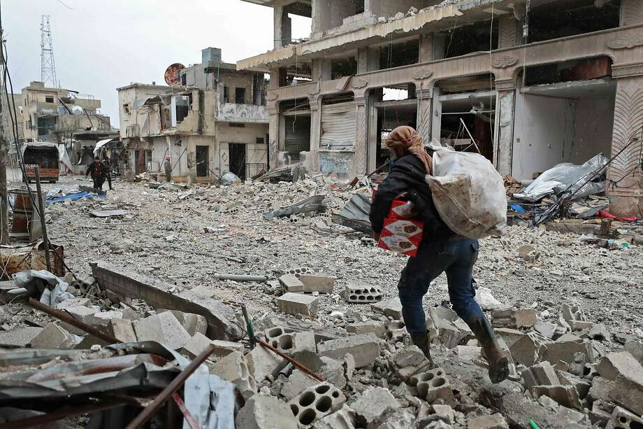 Residents gather belongings in Sarmin in Idlib province after it was shelled by government forces. Photo: Omar Haj Kadour / AFP Via Getty Images