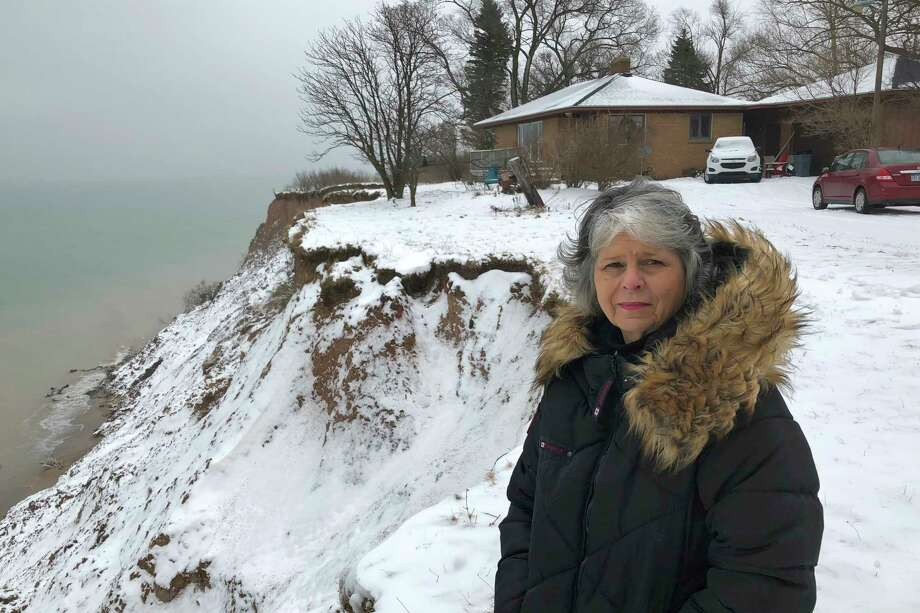 In this Jan. 14, 2020, photo, Rita Alton stands next to her house on the edge of a cliff overlooking Lake Michigan near Manistee, Mich. When her father built the 1,000-square-foot, brick bungalow in the early 1950s, more than acre of land lay between it and the drop-off overlooking the water. But erosion has accelerated dramatically as the lake approaches its highest levels in recorded history, hurling powerful waves into the mostly clay bluff. (AP Photo/John Flesher) / Copyright 2020 The Associated Press. All rights reserved.