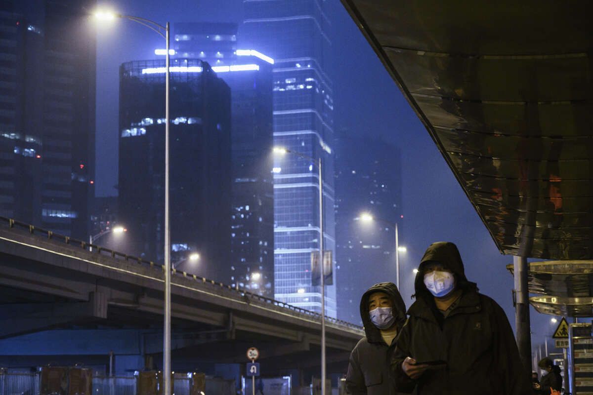 Men wear protective masks and check their phones while waiting for the bus on a nearly empty street on Feb. 7, 2020 in Beijing. The new coronavirus identified in China has spread rapidly since its emergence at the beginning of 2020. Read through to follow the progress of the outbreak response.