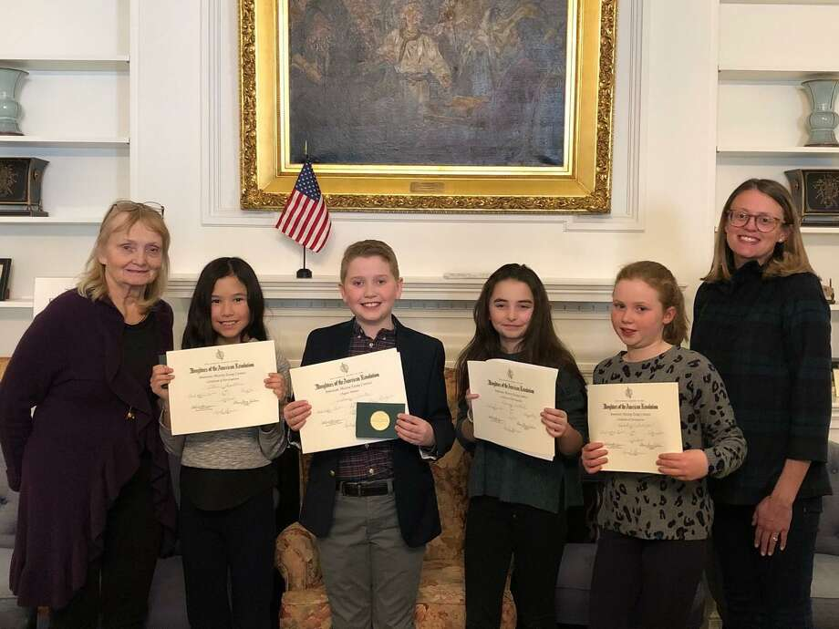 Essay chairman/contest coordinator Sandi MacPherson, left, presented gift certificates from Barrett Bookstore and a DAR certificate to fifth grade essay contest winners including honorable mention Ellie Shpetner from Royle and first place winner, William Curtis from Ox Ridge. Photo: Contributed /
