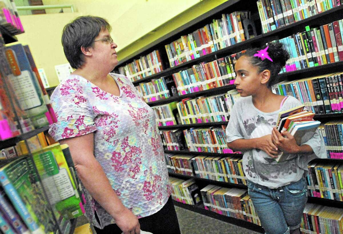 A young patron talks with Sharon Cerasoli, children's librarian at the Russell Library after selecting a handful of books in Middletown. The library just announced it will no longer be imposing fines on overdue items.