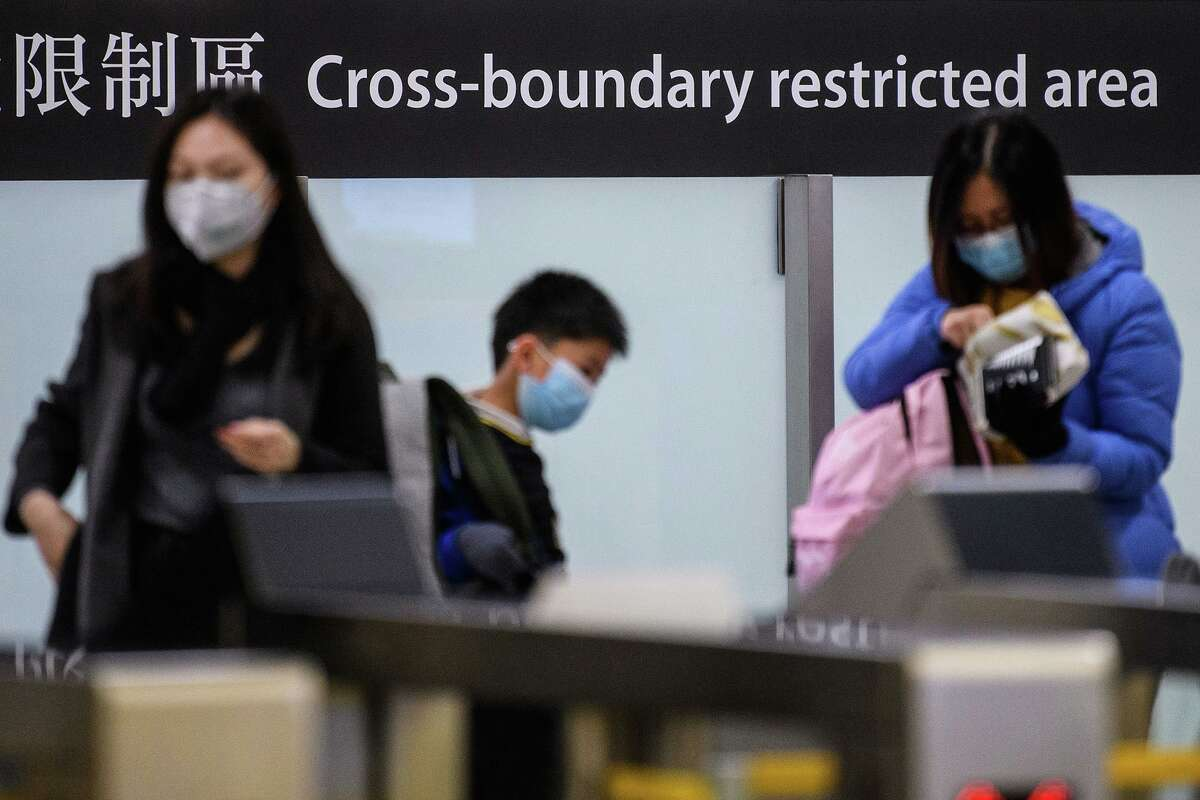 Commuters arriving in Hong Kong wear facemasks as they pass the cross boundary restricted area inside the high-speed train station connecting Hong Kong to mainland China during a public holiday in celebration of the Lunar New Year in Hong Kong on Jan. 28, 2020, as a preventative measure following a virus outbreak which began in the Chinese city of Wuhan. (Anthony Wallace/AFP/TNS)