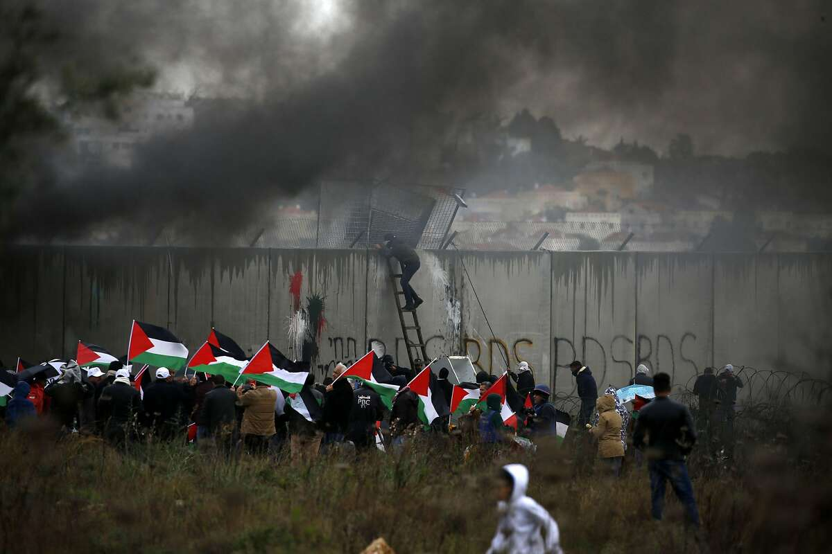 TOPSHOT - A Palestinian protester escalates Israel's controversial security wall as others waving national flags burn tyres during a demonstration against a US-brokered peace proposal, in the occupied West Bank village of Bilin near Ramallah on February 7, 2020. The Jewish settlement of Modiin Illit can be seen in the background. - Israel deployed additional forces in Jerusalem and the occupied West Bank ahead of weekly Muslim Friday prayers, a day after a deadly uptick in violence. The rise in violence comes a week after US President Donald Trump released a long-delayed plan for the Middle East that angered the Palestinians. (Photo by ABBAS MOMANI / AFP) (Photo by ABBAS MOMANI/AFP via Getty Images)