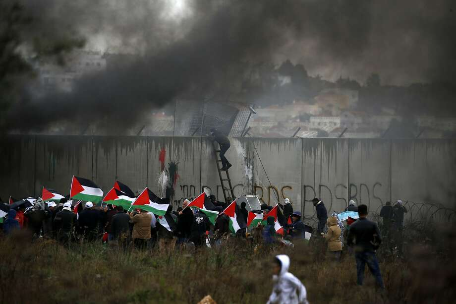Palestinian protesters gather along Israel's controversial security wall, waving national flags and burning tires during a demonstration in the occupied West Bank village of Bilin. Photo: Abbas Momani / AFP Via Getty Images