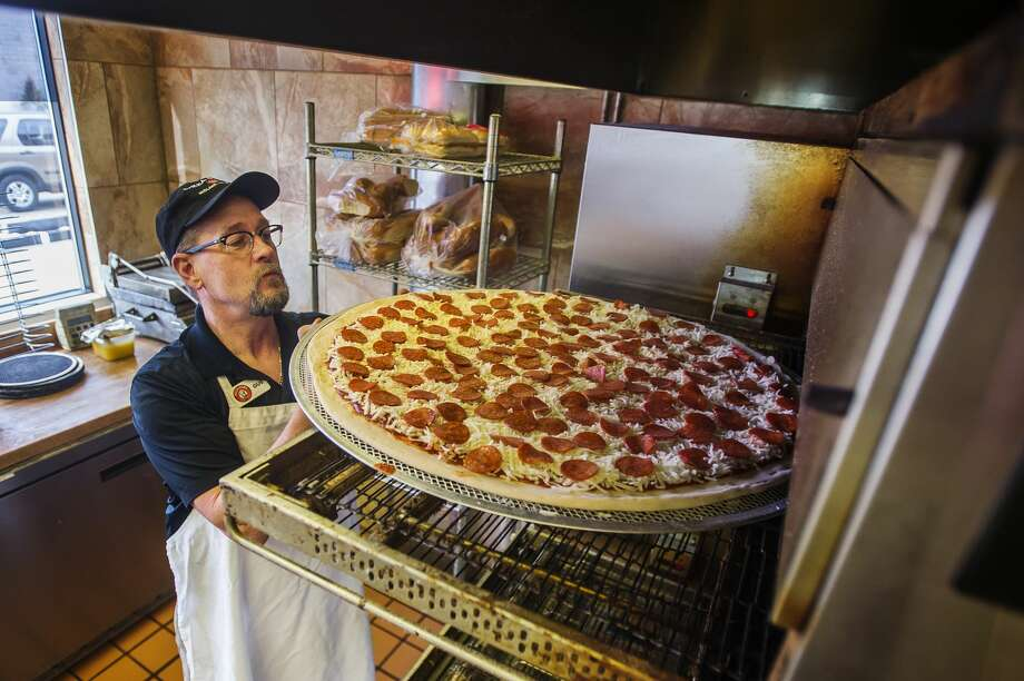 Gus Wojda, owner and general manager of Pizza Sam's, places one of the restaurant's new 28-inch pizzas into an oven in preparation of a pizza eating contest hosted by the Midland Daily News and Pizza Sam's Monday, Feb, 3, 2020 at the restaurant. (Katy Kildee/kkildee@mdn.net) Photo: (Katy Kildee/kkildee@mdn.net)