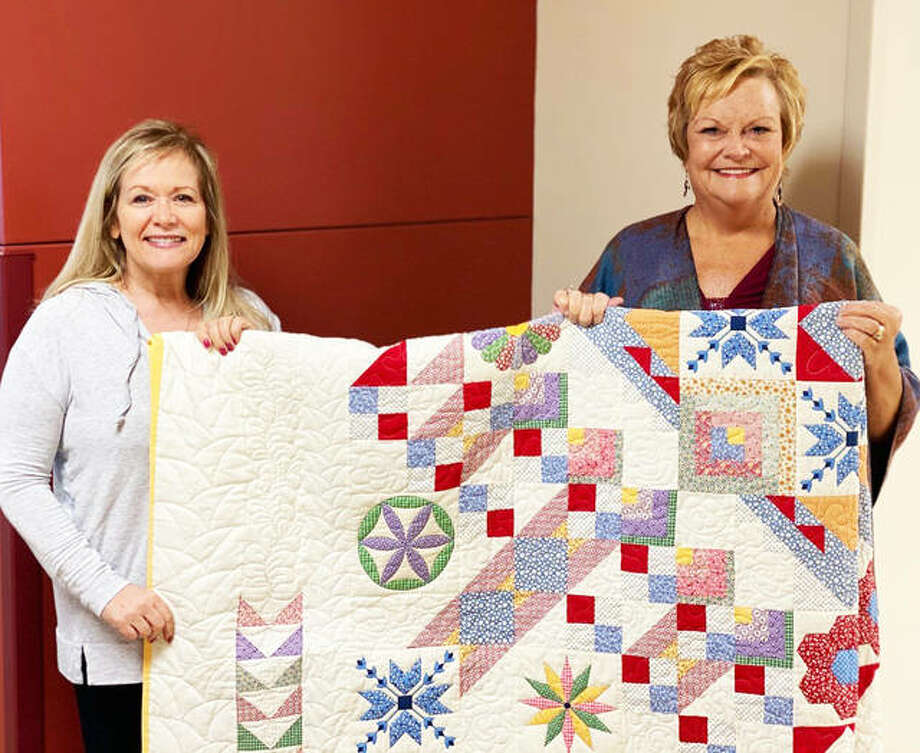 Shipman's Barb Erwin, left, holds the queen-size quilt she won in the Carlinville Area Hospital Auxiliary's winter fundraising raffle. Helping her is Auxiliary President Rhonda Caveny-Jones. The raffle generated $1,780. Photo: For The Telegraph
