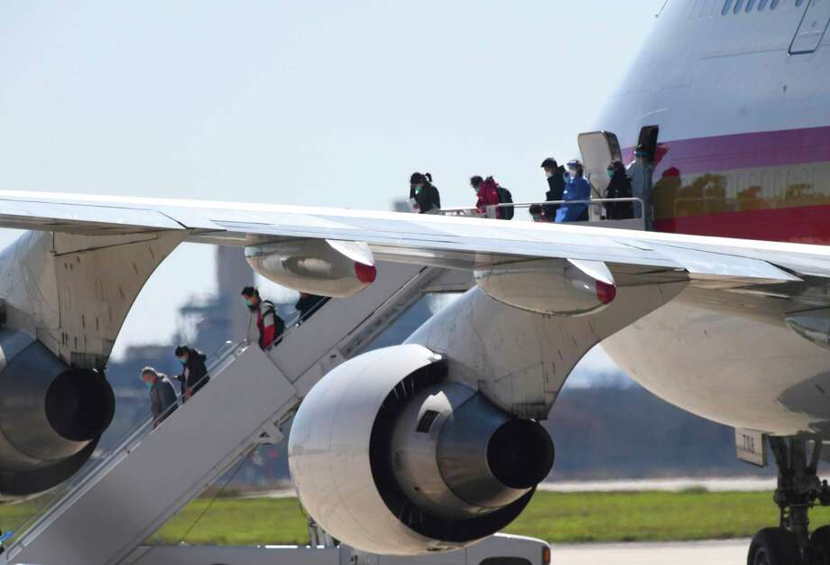 People at risk of carrying the coronavirus arrive at Joint Base San Antonio-Lackland aboard a chartered Boeing 747 on Friday, Feb. 7, 2020. Photo: Billy Calzada /Staff Photographer / ***MANDATORY CREDIT FOR PHOTOG AND SAN ANTONIO EXPRESS-NEWS /NO SALES/MAGS OUT/TV
