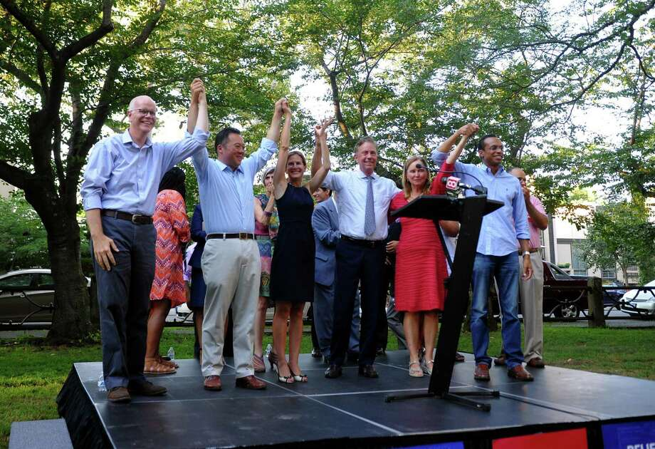Democratic candidates including Susan Bysiewicz and Ned Lamont, standing in center, as well as other elected officials raise their arms to the crowd gathered for a unity rally at Wooster Square Park in New Haven in 2018. From left to right is Connecticut state Comptroller Kevin Lembo, candidate for Attorney General William Tong, Bysiewicz, Lamont, Secretary of the State Denise Merrill and candidate for Connecticut State Treasurer Shawn Wooden. Photo: Christian Abraham / Hearst Connecticut Media / Connecticut Post