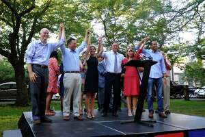 Democratic candidates including Susan Bysiewicz and Ned Lamont, standing in center, as well as other elected officials raise their arms to the crowd gathered for a unity rally at Wooster Square Park in New Haven in 2018. From left to right is Connecticut state Comptroller Kevin Lembo, candidate for Attorney General William Tong, Bysiewicz, Lamont, Secretary of the State Denise Merrill and candidate for Connecticut State Treasurer Shawn Wooden.