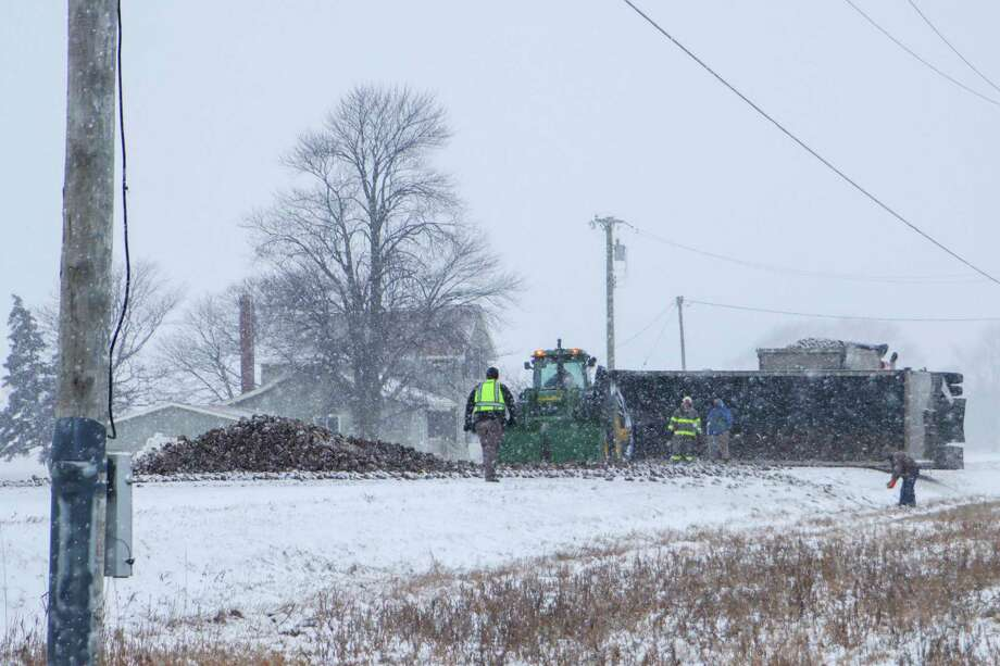 Crews work to clean the roadway after a trailer hauling sugar beets overturned due to icy road conditions Feb. 7. (Scott Nunn/Huron Daily Tribune)
