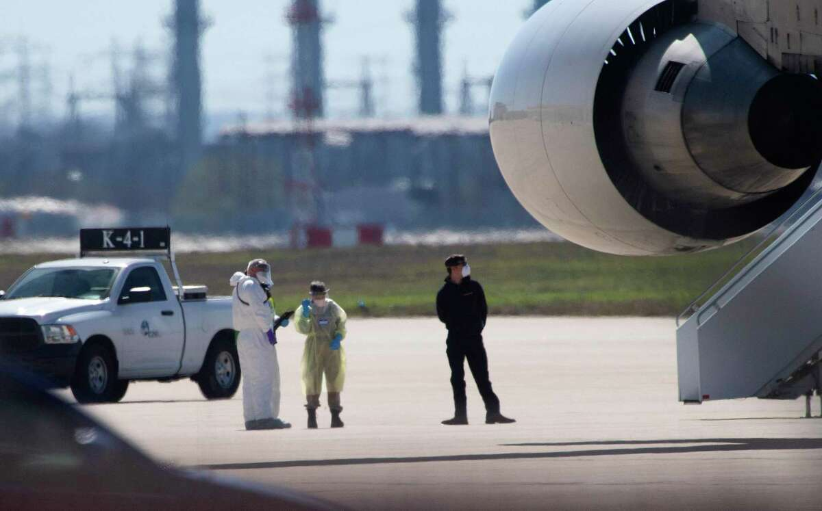 Personnel in hazmat suits wait for people at risk of carrying the coronavirus to disembark from a chartered Boeing 747 at Joint Base San Antonio-Lackland on Friday, Feb. 7, 2020.