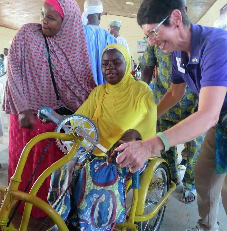 Wheelchair recipient is assisted into her new wheelchair by a Rotarian and her friend at a wheelchair distribution ceremony in Jos Nigeria. (Courtesy Photo)