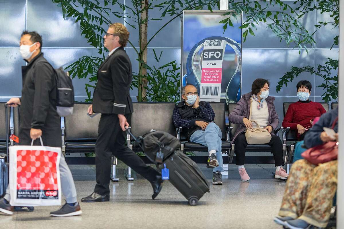 Passengers arrive at SFO from international flights on Friday, February 7, 2020 in San Francisco, Calif. SFO and its businesses have seen a 2.5% reduction in total passenger traffic and flight cancellations to China because of the coronavirus outbreak.