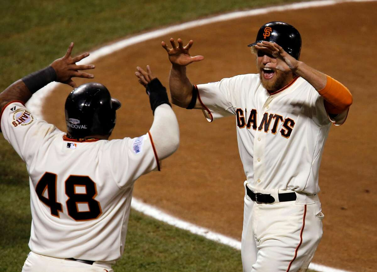Giants Pablo Sandoval and Hunter Pence celebrate scoring on a Juan Perez two-run RBI double in the eighth inning during game five of the World Series at AT&T Park in San Francisco, California, on Sunday Oct. 26, 2014.