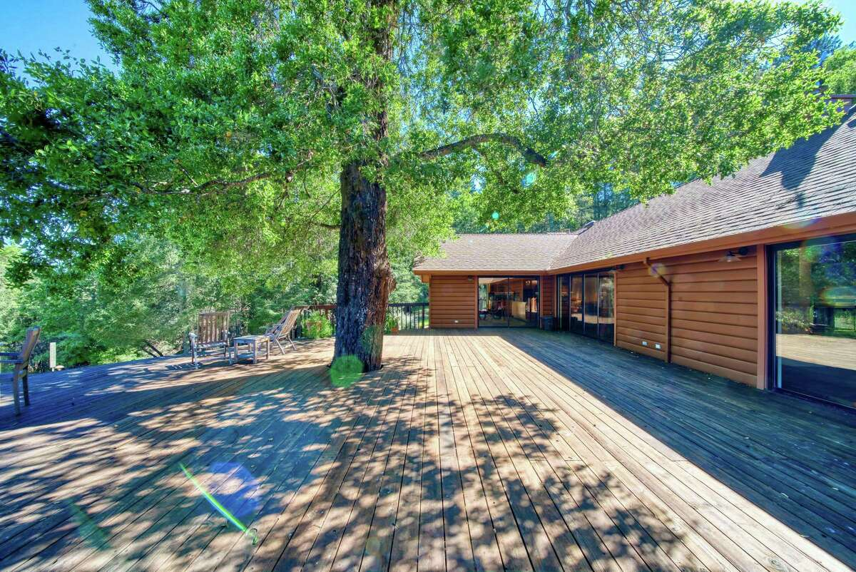 A mature tree shades the rear deck of 3460 Mount Veeder Road in Napa, a four-bedroom set on a 21.7-acre estate with two acres of fallow vineyard.
