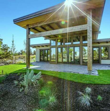 An extended eave shelters the rear patio of 22956 Ghost Tree Lane in Bend, Oregon, a two-bedroom, two-bathroom home within the Pronghorn Resort.