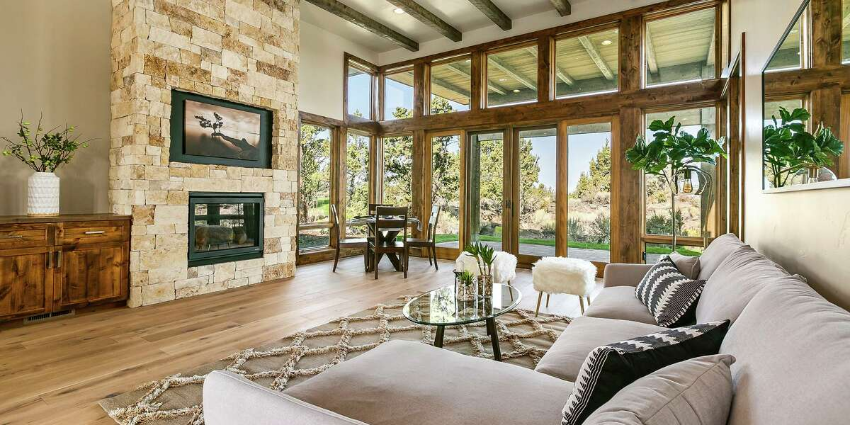 The living room of 22956 Ghost Tree Lane in Bend, Oregon includes a gas fireplace, beamed ceiling and glass doors opening to a paver patio.
