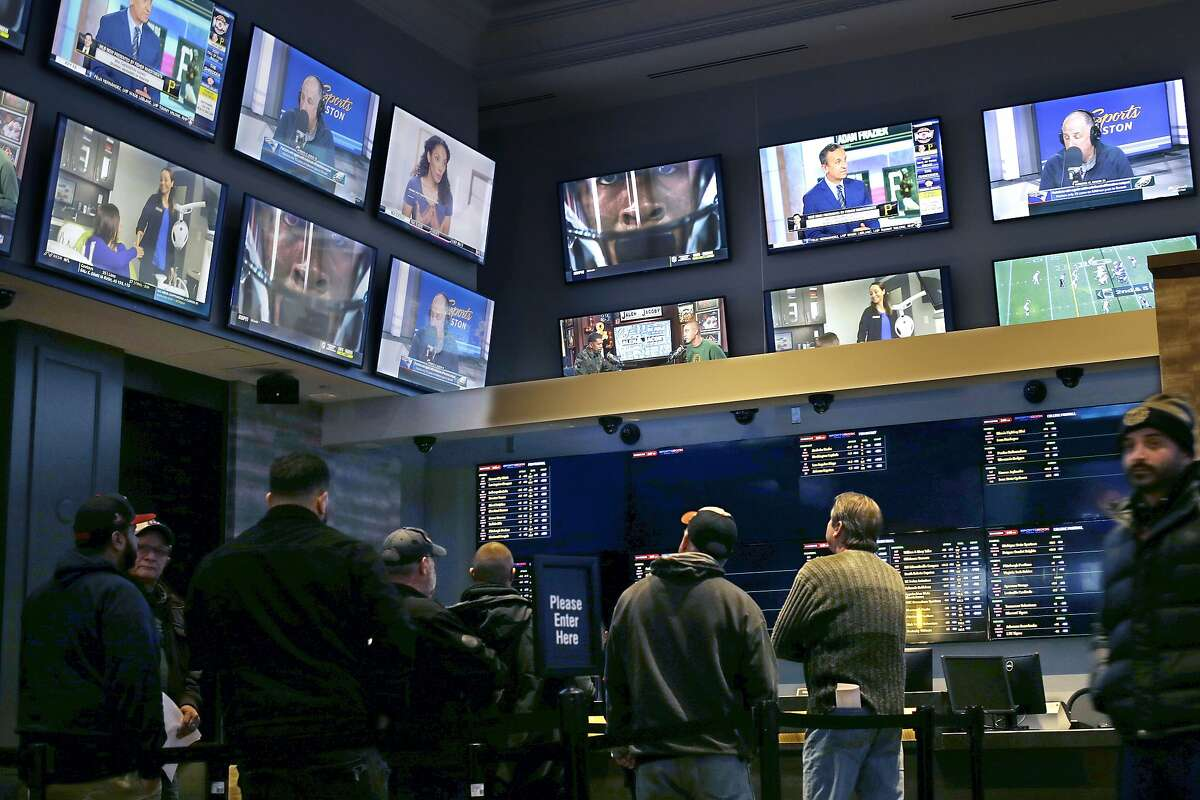 FILE - In this Nov. 18, 2019, file photo, patrons visit the sports betting area of Twin River Casino in Lincoln, R.I. Gambling regulators and sports books in several U.S. states are preparing to allow gamblers to bet on XFL games once the league's season begins in early February 2020. (AP Photo/Steven Senne, File)