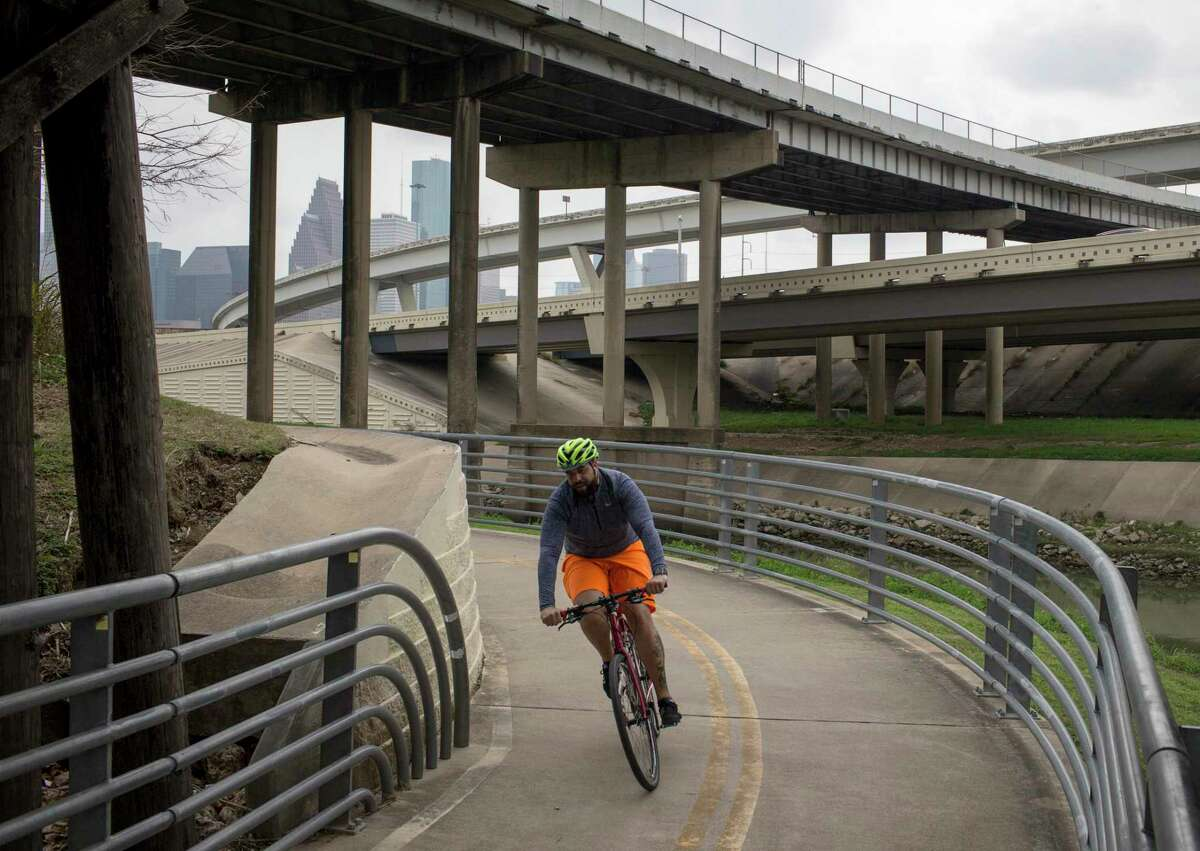 A cyclist rides along the White Oak Bayou Greenway Trail on Tuesday, Feb. 4, 2020, at in Houston. In the background, Hogan Street crosses over IH-45, north of Downtown Houston.