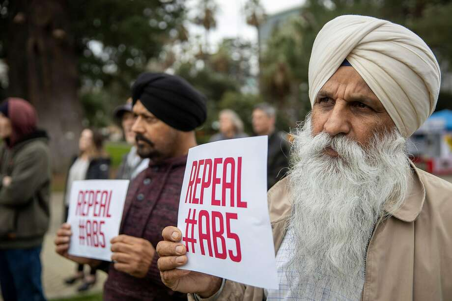 Truck drivers Avtar Singh and Amrik Singh stand with a group of independent freelancers during a rally of people seeking to repeal AB5 in Sacramento in January. Photo: Peter DaSilva / Special To The Chronicle
