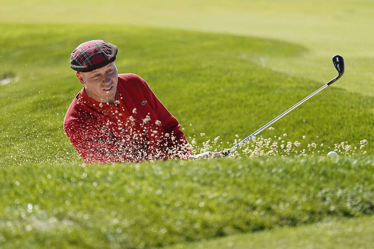 Rapper Macklemore hits out of a bunker on the sixth green of the Monterey Peninsula County Club Shore Course during the second round of the AT&T Pebble Beach National Pro-Am golf tournament Friday, Feb. 7, 2020, in Pebble Beach, Calif. (AP Photo/Tony Avelar)
