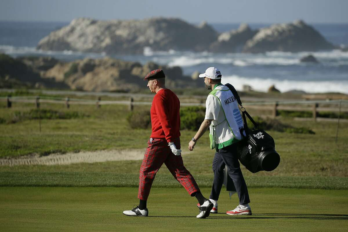 Macklemore walks with his caddie along the 12th fairway of the Monterey Peninsula Country Club Shore Course during the second round of the AT&T Pebble Beach National Pro-Am golf tournament Friday, Feb. 7, 2020, in Pebble Beach, Calif. (AP Photo/Eric Risberg)