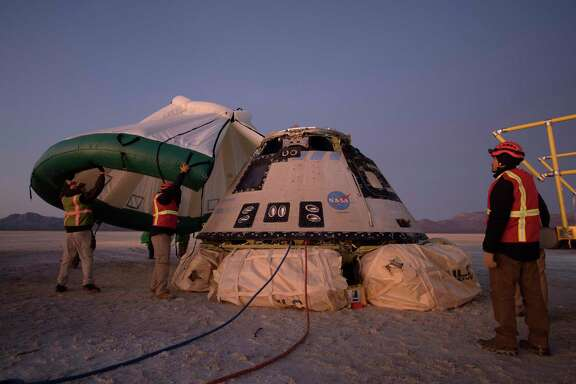 In this Sunday, Dec. 22, 2019 photo made available by NASA, Boeing, NASA, and U.S. Army personnel work around the Boeing Starliner spacecraft shortly after it landed in White Sands, N.M. (Bill Ingalls/NASA via AP)