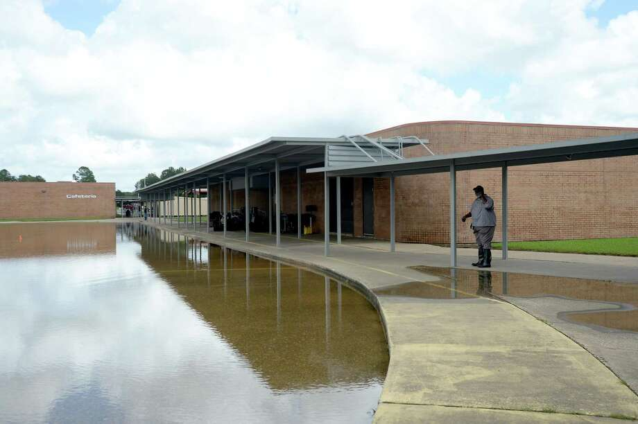 A maintenance worker talks on his phone after waslking through the grounds at Hamshire-Fannett Middle School, where every building on campus sustained flood damage from Imelda's heavy rainfall Thursday. District and school personnel were at the site evaluating the damage and meeting with contractors to begin the renovation process. School will be cancelled next week as they also formulate a plan for where students will go to continue classes this year. Photo taken Saturday, September 21, 2019 Kim Brent/The Enterprise Photo: Kim Brent / The Enterprise / BEN